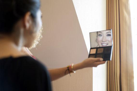 Bride looking in make up mirror