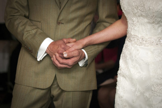 Bride and groom hold hands during service