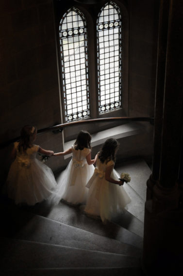 3 bridesmaids walk down old staircase