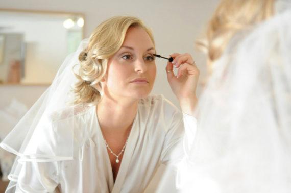 Bride applies makeup in mirror