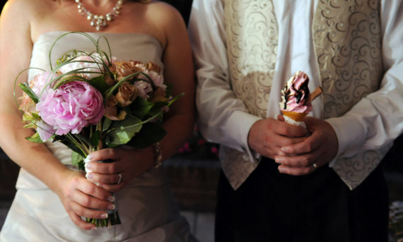 Brides hands with bouquet and groom holds icecream